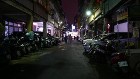 POV walk through dark Taipei street, few local people on way, dim illumination Footage
