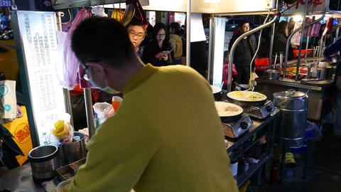 Cook chinese pancake on night street stall vire from behind kitchener Footage