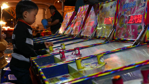 Child play pinball at gaming machine, outdoor amusement zone, close up side view Footage