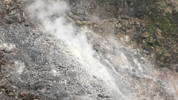 Opaque white smoke rises from the dry fumarole, stony inclined slope Footage