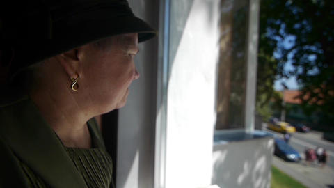 Woman looks out the window awaiting guests 98 Footage
