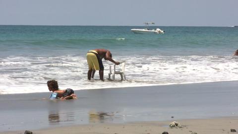 Man washing chair on beach Footage