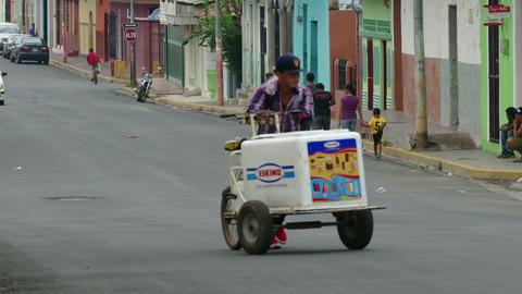 Ice cream man walks along the street Footage