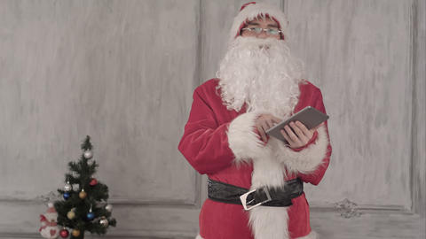 Santa Claus using tablet computer on White Background Footage