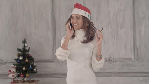 Pretty young Caucasian woman with Santa hat talking smartphone Footage