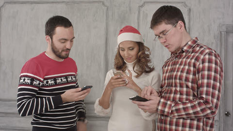 Three friends use their cell phones on a white background Footage