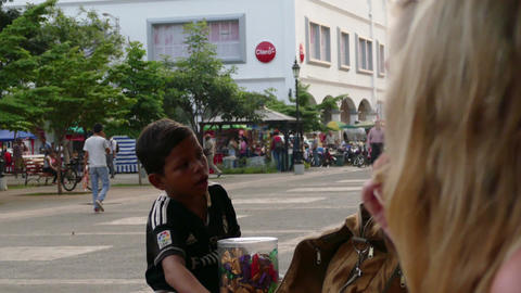 Little boy trying to sell candy in the street Live Action
