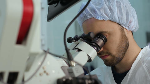 Young doctor using loking at eyepieces of microscope complex system in a hospita Footage