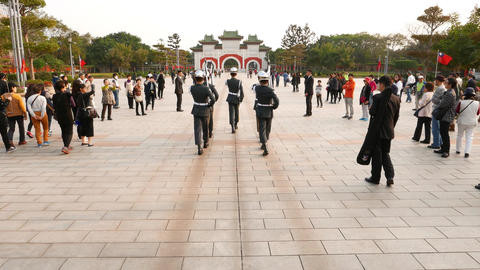 Soldiers march at square to gate, tourists flock around ceremony