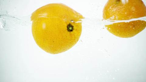 Two Tangerines Being Splashed into Water in Super Slow Motion Footage