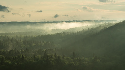 Time lapse of mist rising over a valley as the Sun sets Footage