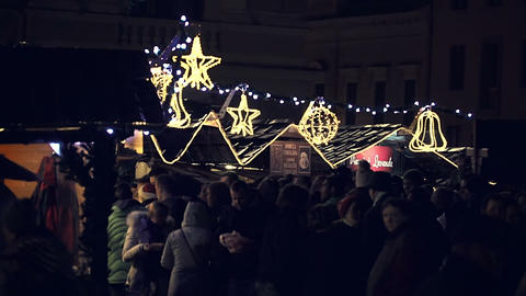 People at christmas marketplace with lights and stands in background Footage