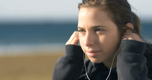 Putting headphones to her ears to listen to music Footage