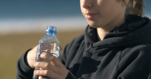 Girl drinking fresh natural water from a plastic bottle Footage