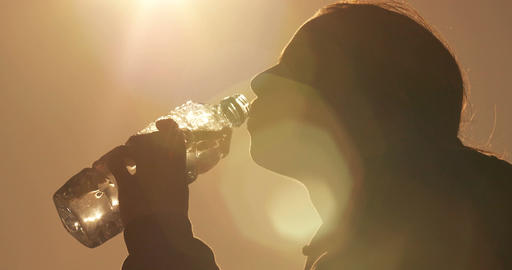 Fitness woman drinking fresh water from a plastic water outdoors in park Footage