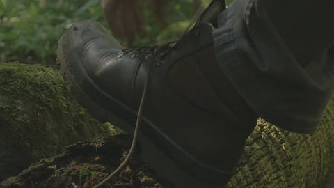 Tying hiking boot shoe laces Man Hiking Through A Forest Outdoors Day Footage