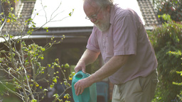 Gardening elderly Senior retired grandfather at man retirement age outdoors Live Action