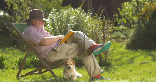 Elderly retired man relaxing outdoors reading a book enjoying retirement Live Action