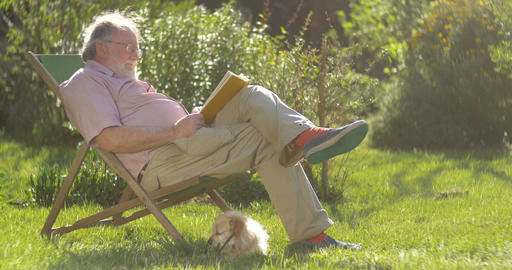 Retired elderly man and dog relaxing outdoors reading a book enjoying retirement Live Action