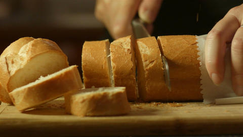 fresh golden brown bread cutting up in kitchen on bread board Footage