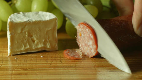 camembert brie cheese cheese and salami platter prep cutting up in kitchen Footage