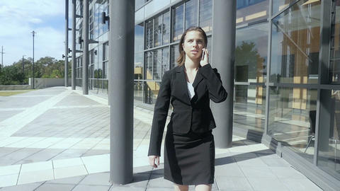 Business woman walking talking on phone outside building Slow motion Footage