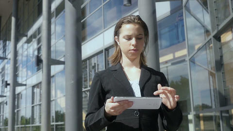 Business woman walking using tablet pc outside building Slow motion Footage