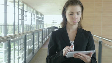 Slow motion businesswoman walking in office building working on tablet pc ipad Footage
