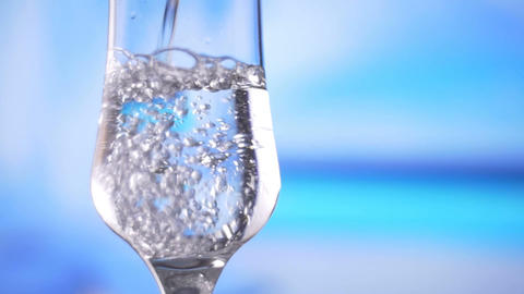 Water pouring into glass slow motion fresh natural cool with bubbles Footage