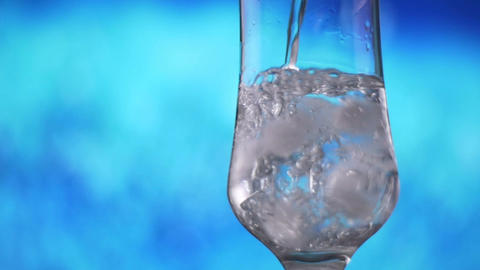 Water pouring into glass with ice slow motion fresh natural cool with bubbles Footage