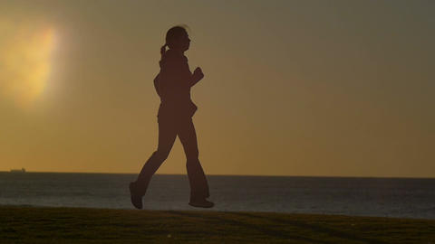 Sporty Girl Jogging in the park sunrise / sunset slow motion Footage
