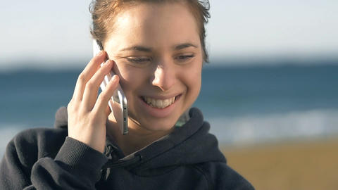 Happy Girl talking on phone smiling outdoors In sunshine Footage
