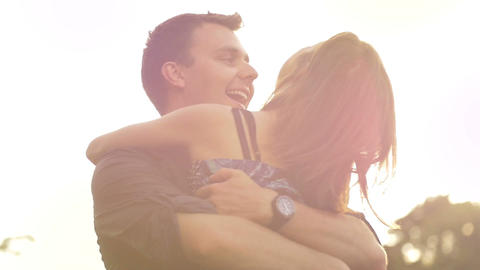 Young couple in love hugging laughing being happy outdoors sunset lifestyle Footage