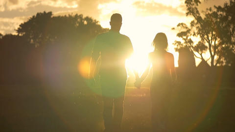 Young couple in love holding hands walking sunset heterosexual lifestyle Footage