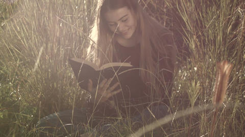 Reading Book Young Teenage Girl Sitting In Grass Relaxing Outdoors In Sun stock footage
