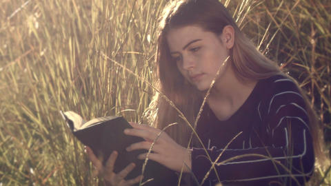 Reading book young teenage girl sitting in grass relaxing outdoors in sun Footage