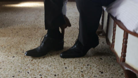 man in white wedding shirt puts on black shoes ties shoe-laces Footage