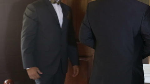 man helps groom to put on tuxedo in front of mirror Footage